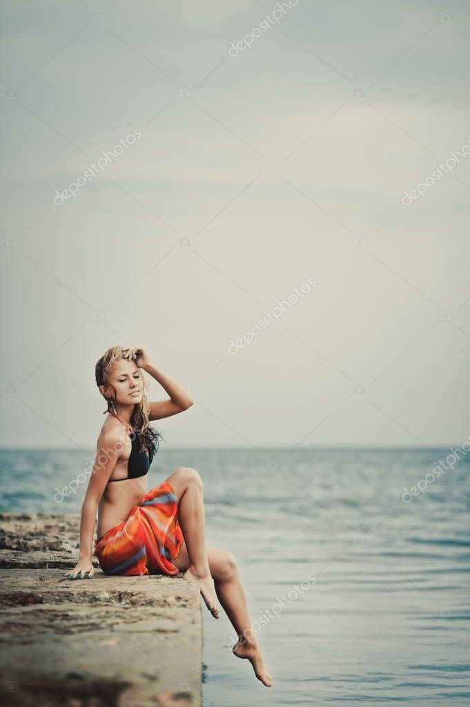 A girl in a swimsuit on a pier
