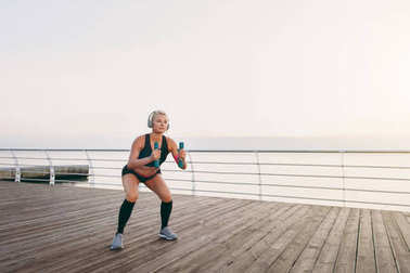 Young beautiful athletic girl with long blond hair in headphones, listening to music and crouching with dumbbells at sunrise over the sea
