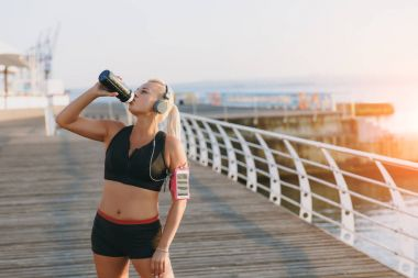 Young beautiful athletic girl with long blond hair in headphones drinks water from a bottle at dawn by the sea