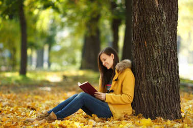 A beautiful happy smiling brown-haired woman in yellow coat and jeans sitting under the maple tree with a red book in fall city park on a warm day. Autumn golden leaves. Reading concept