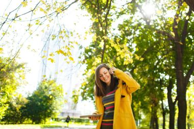 A beautiful happy cheerful brown-haired woman in a yellow coat and striped longsleeve rejoices with a tablet in her hands and white headphones in fall city park on a warm day. Autumn golden leaves.