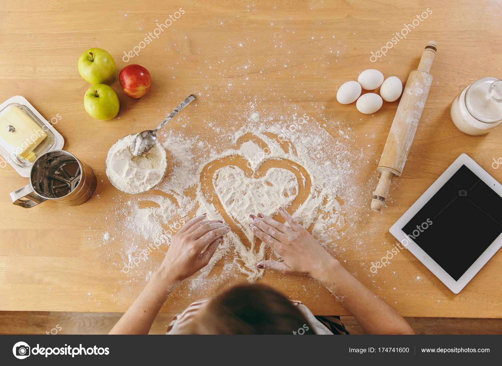 Handgemalte Herzen in Mehl auf dem Küchentisch und anderen Zutaten ...