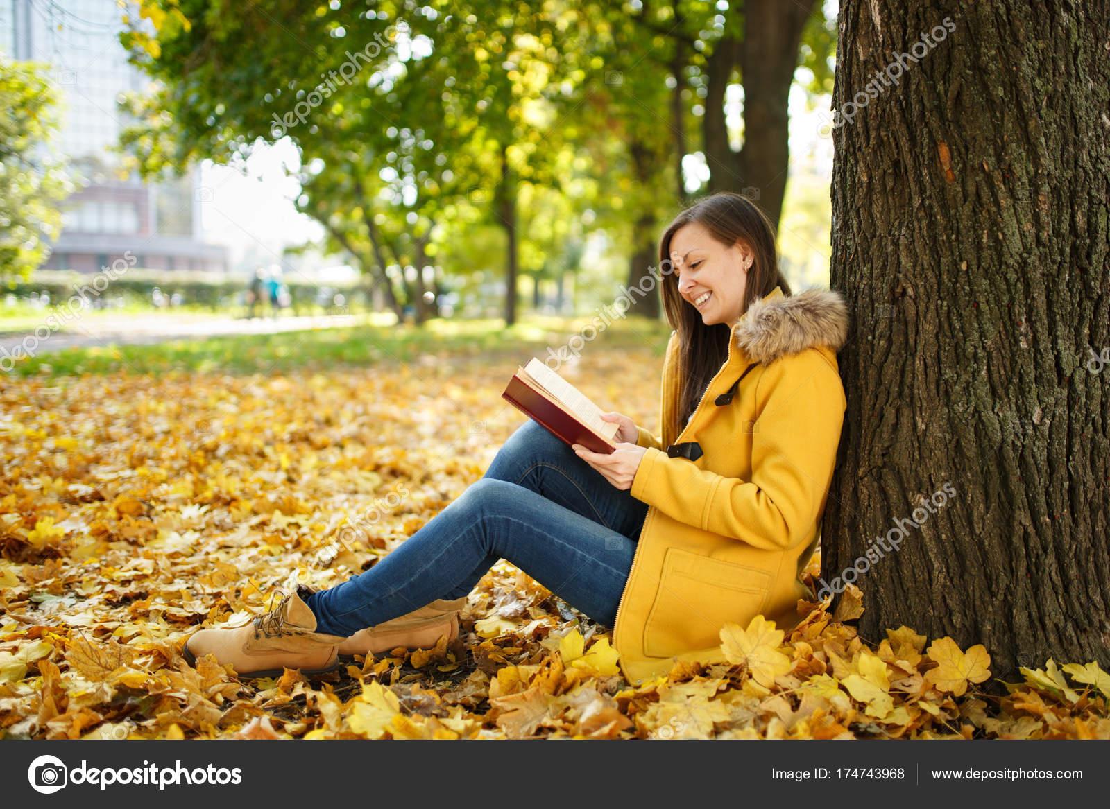 Una feliz sonriente pelo castaño mujer bella capa amarilla y los pantalones  vaqueros sentados debajo del árbol de arce con un libro rojo en el parque  de la ... b4ee879b40e0