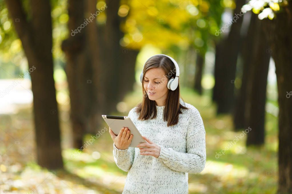A beautiful happy cheerful brown-haired woman in white sweater with a tablet listening music in the white headphones in fall park on a warm day. Autumn in the city.