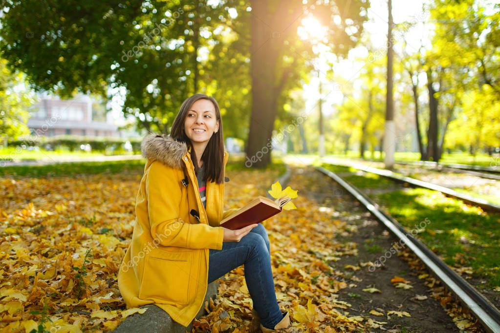 A beautiful happy brown-haired woman in a yellow coat and jeans sits alone in the park near the tram tracks and reads a book in the fall warm day. Autumn yellow leaves.