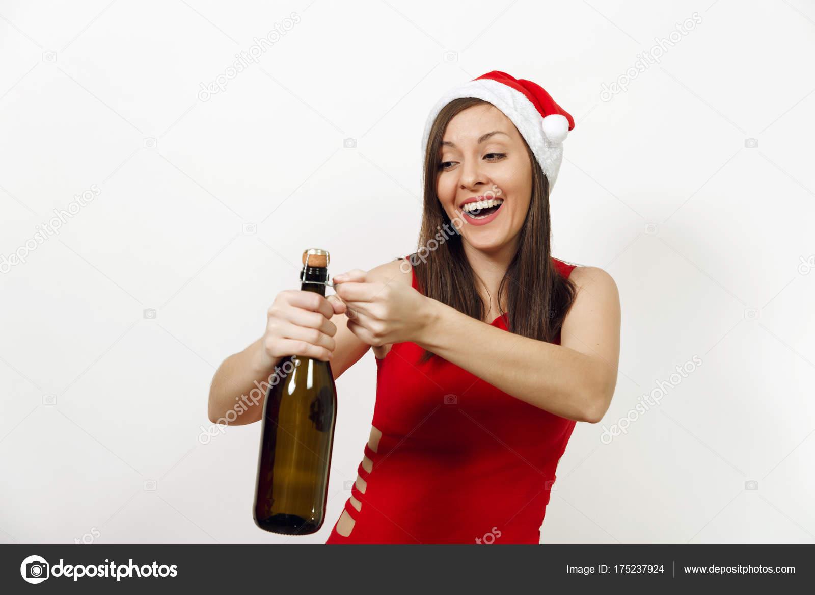 0ecf64f88 ... caucásica feliz joven con sonrisa encantadora en vestido rojo y  sombrero de la Navidad tratando de abrir la botella de champagne sobre fondo  blanco.