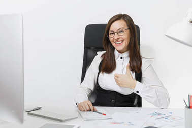Beautiful smiling brown-hair business woman in suit and glasses sitting at the desk, working at computer with modern monitor with documents in light office, showing thumb up on white background