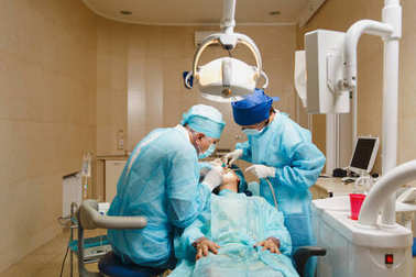 Male old professional dentist surgeon in uniform and female assistant helps to performing operation install dental implant teeth of woman patient in clinic light office with modern tools equipment.
