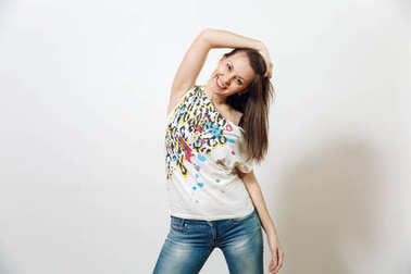 Beautiful European young happy brown-haired woman with healthy clean skin, dressed in casual light clothes looking at camera with shy charming smile, on a white background. Emotions concept.