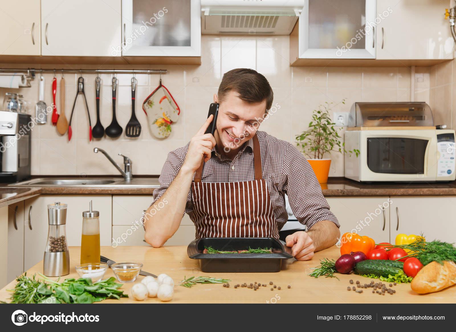Junger Mann in Schürze am Tisch sitzen, mit Gemüse, telefonieren mit ...