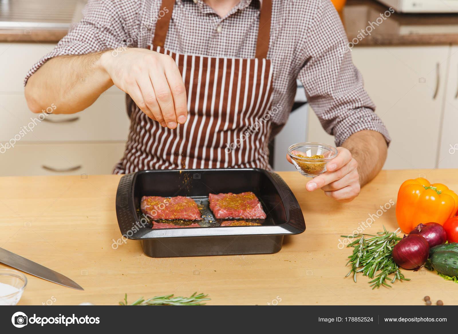 Mann in Schürze am Tisch sitzen, mit Gemüse, Fleisch würzen in ...