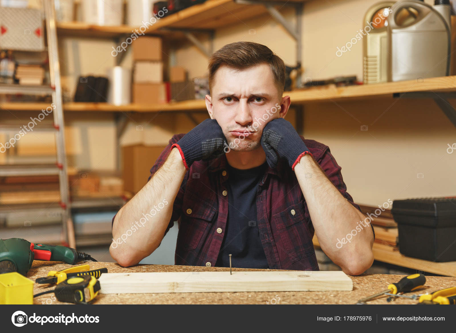 4252a261 Handsome sad upset caucasian young man in plaid shirt, black T-shirt,  gloves working in carpentry ...