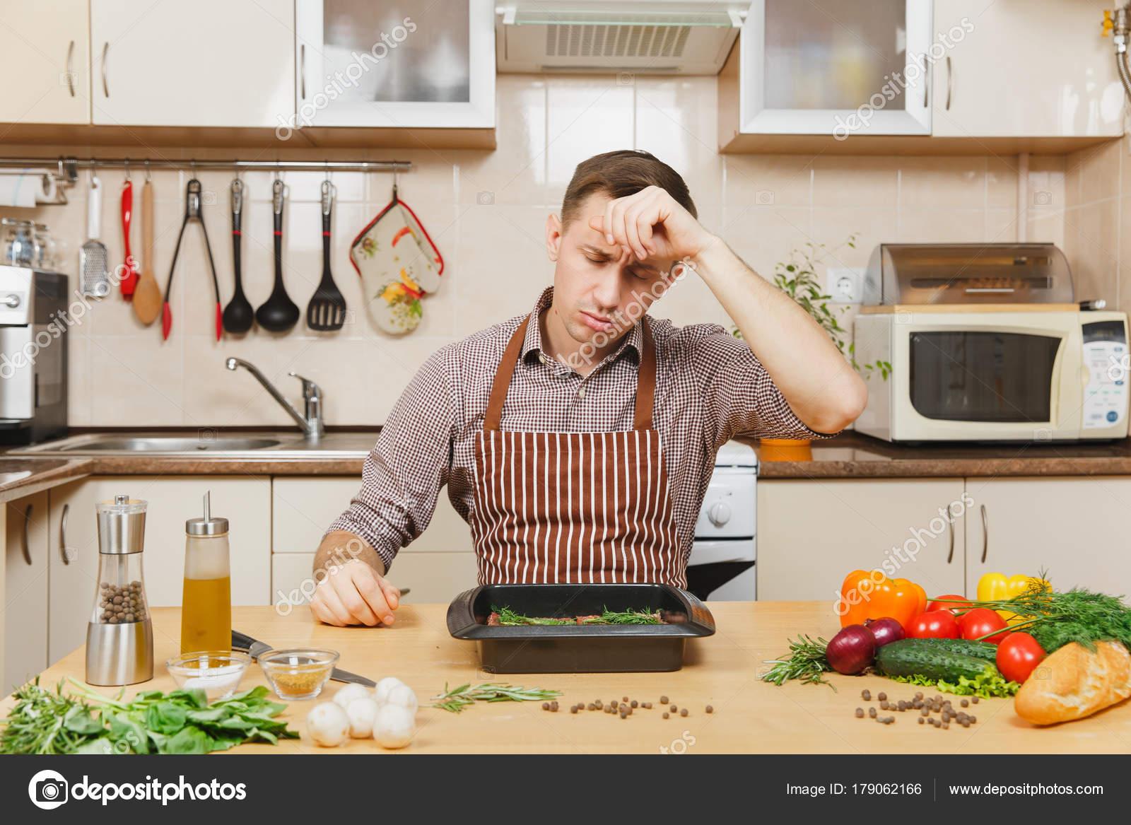 Müde Stress verärgert Jüngling in Schürze mit Gemüse, am Tisch ...