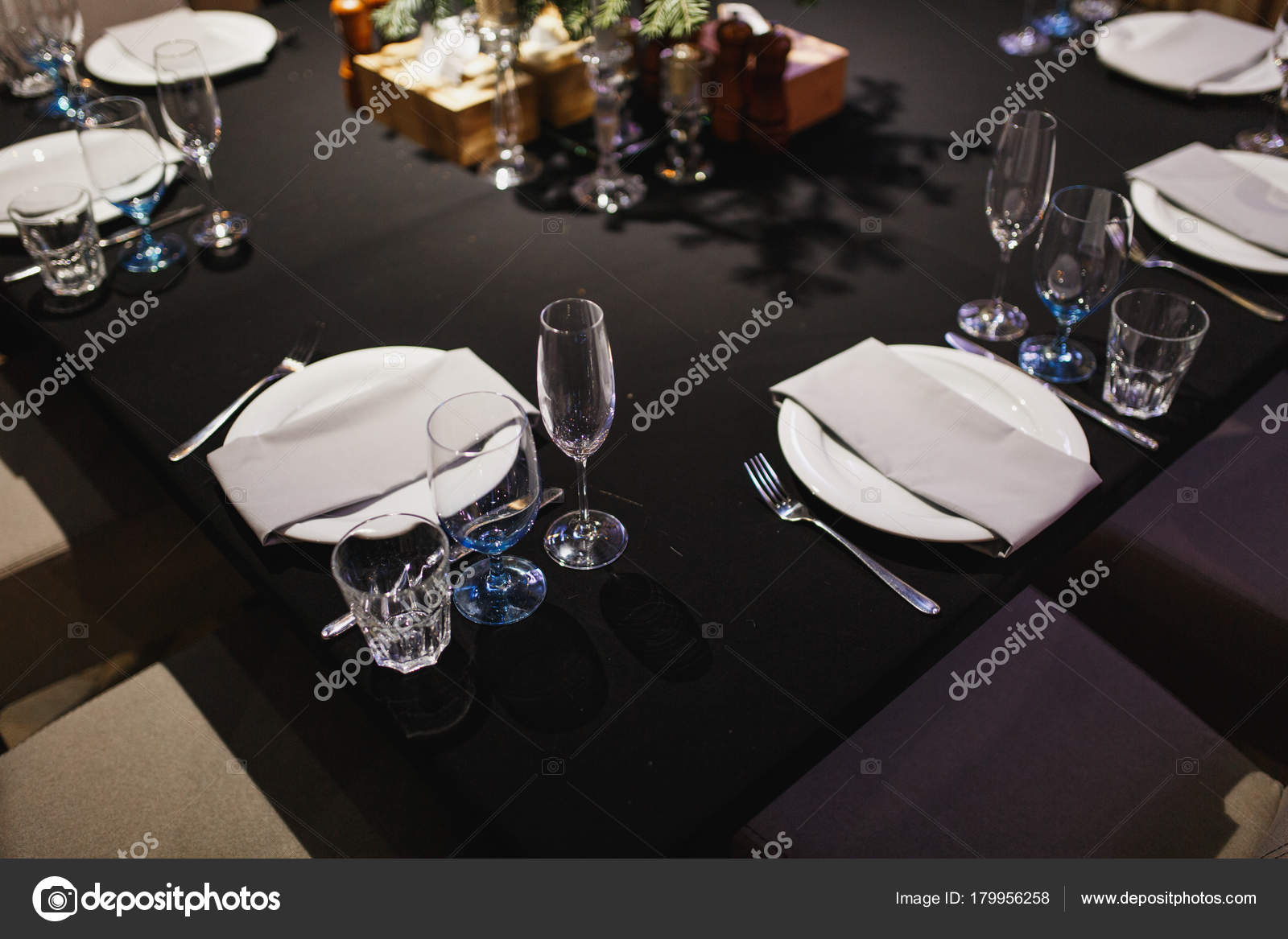 ... candles and decorative flower on dark black tablecloth on table served for dinner in cozy restaurant. Empty served restaurant table with plates wine ... & Close up glasses forks knives napkins candles and decorative ...