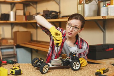 Beautiful caucasian young brown-hair woman in plaid shirt, gray T-shirt, yellow gloves making toy car iron model constructor, working in carpentry workshop at wooden table place with different tools.