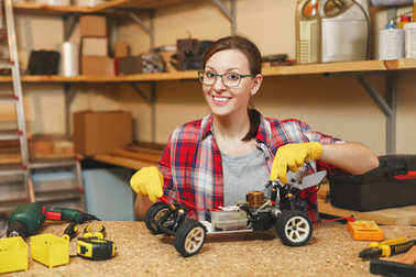 Young woman in plaid shirt, gray T-shirt, yellow gloves making toy car iron model constructor, working in carpentry workshop at wooden table place with different tools. Multimeter for electrician.
