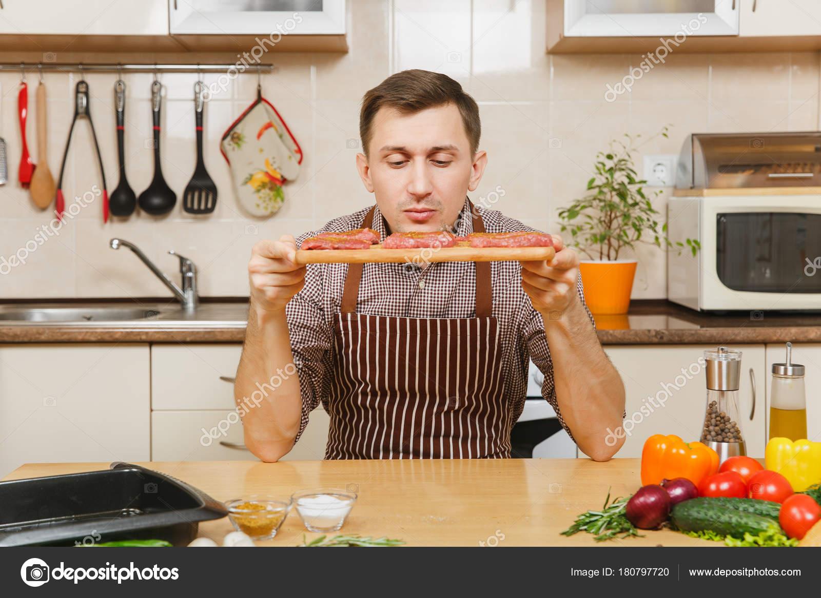 Junger Mann in Schürze am Tisch sitzen, mit Stücken von Fleisch auf ...