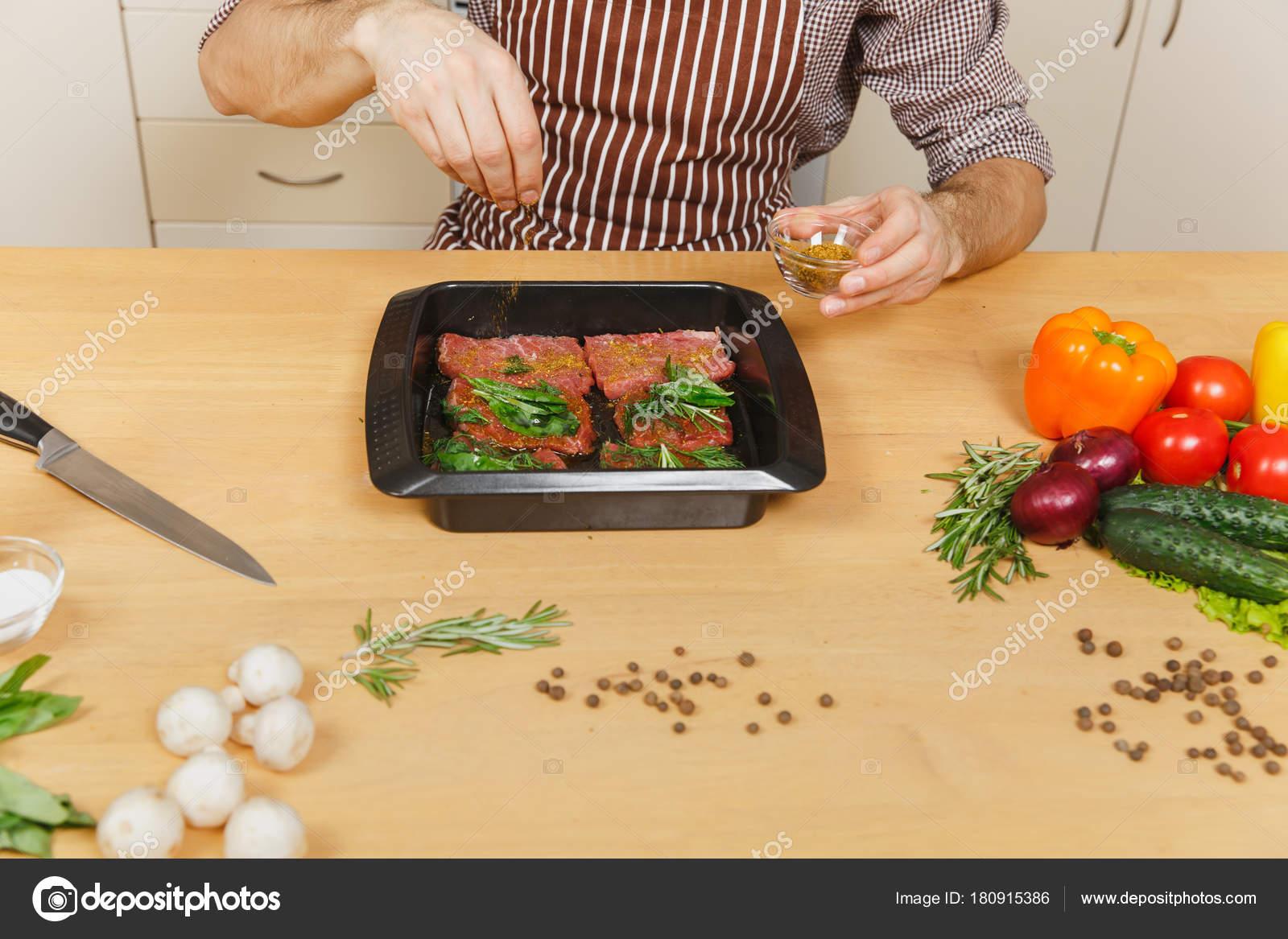 Close-up-junger Mann in Schürze mit Gemüse, am Tisch sitzen zu Hause ...