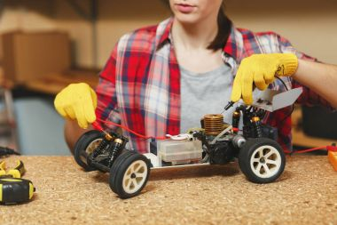 Young woman in plaid shirt, gray T-shirt, yellow gloves making toy car iron model constructor, working in workshop at wooden table place with different tools. Close up multimeter for electrician.