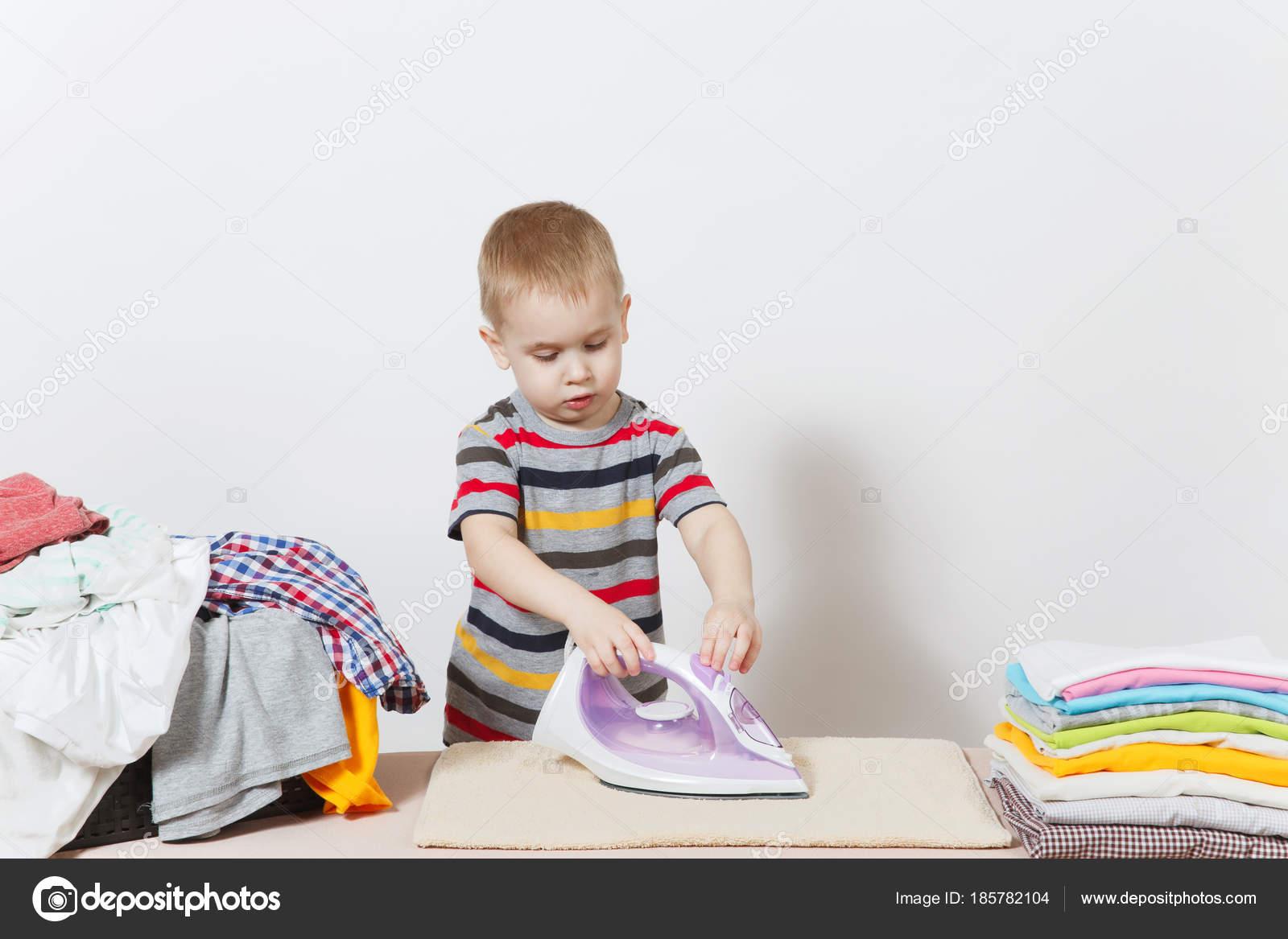 Happy little boy ironing family clothing on ironing board