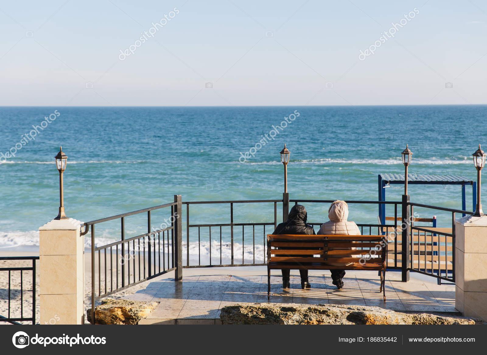 Vista dal retro che un paio in vestiti caldi si siede su una panca