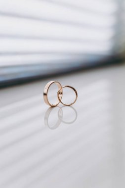 Close up Two beautiful stylish gold wedding rings of the bride and groom intersect on a white gloss windowsill background. Wedding accessories, jewelry