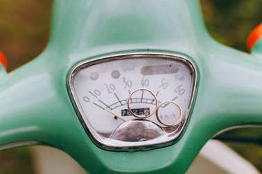 Close up Two beautiful stylish broad wedding rings with strips of the bride and groom intersect on speedometer of green scooter in the garden background. Wedding accessories, jewelry