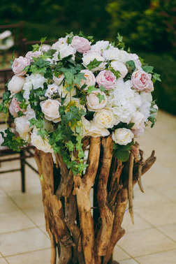 Beautiful decoration of a wedding ceremony in a green autumn garden. Elements decor gentle flower compositions of pink and cream peonies and green leaves placed on the branches