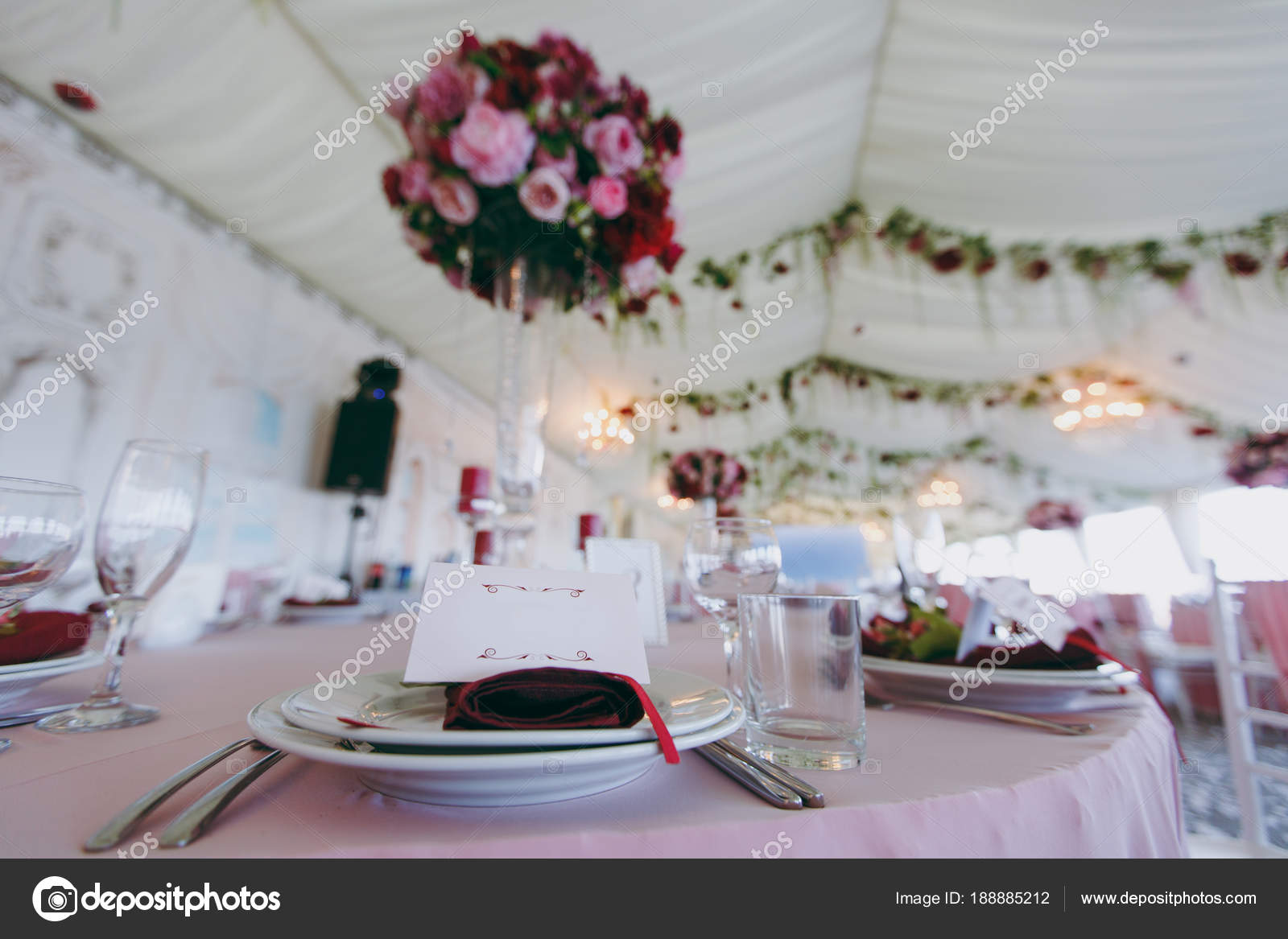 Beautiful decoration of the wedding banquet under the awning in pink burgundy and white tones. Table setting in a hall with plates cutlery glasses ... & Beautiful decoration of the wedding banquet under the awning in pink ...