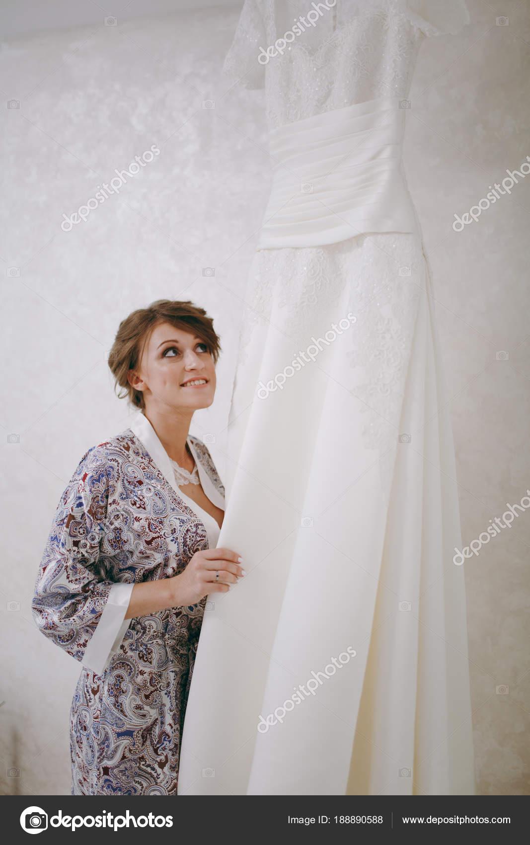 Nevěsta v Vzorované šaty s krásný účes stojí vedle její svatební bílé dlouhé  krajkové šaty 48661b47d0a