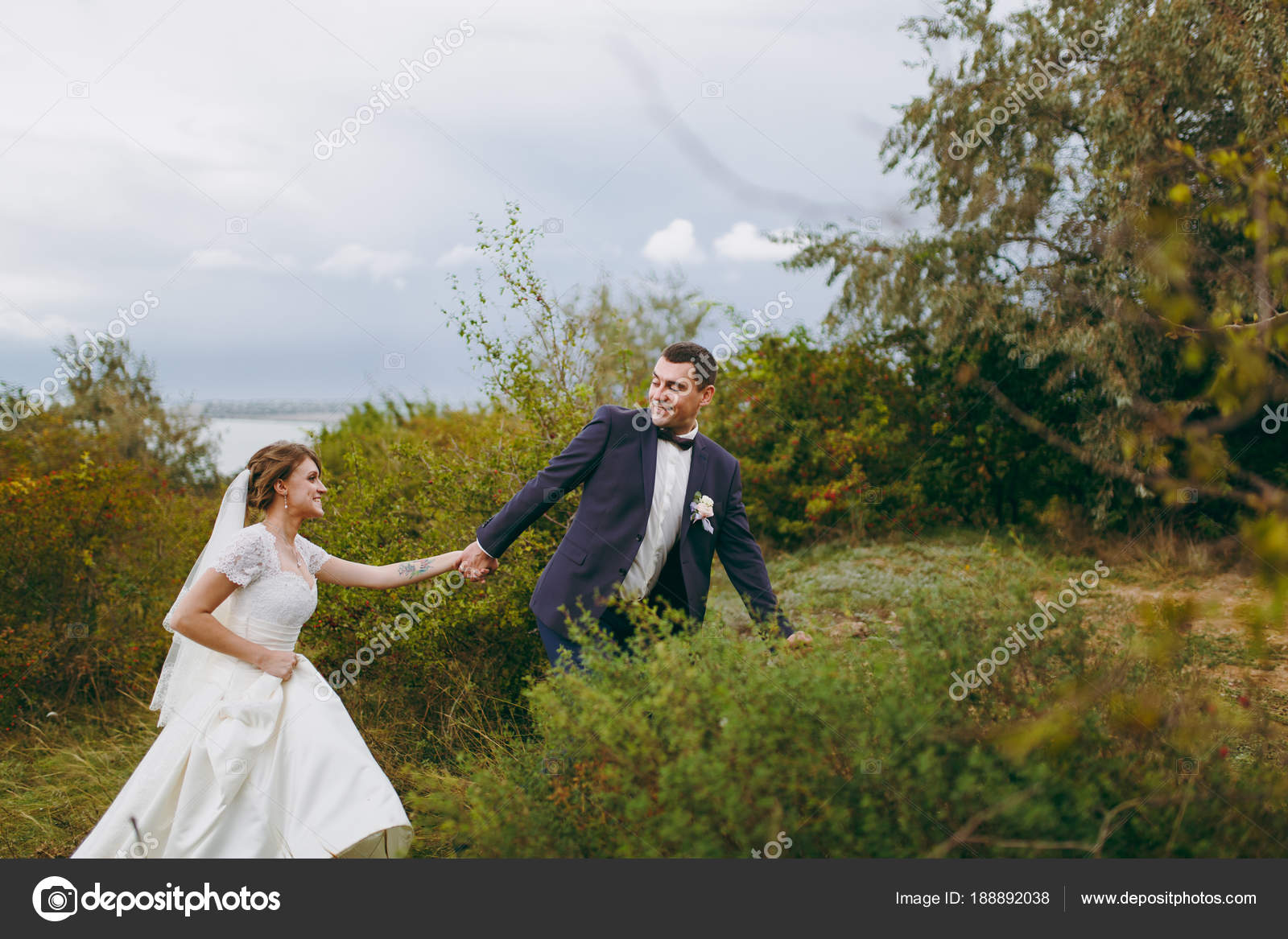 4d0ce12b013a8 Piękny ślub photosession. Przystojny pan młody niebieski garnitur formalne  i muszka z boutonniere i jego elegancki Panna Młoda w białej sukni i welonu  z ...