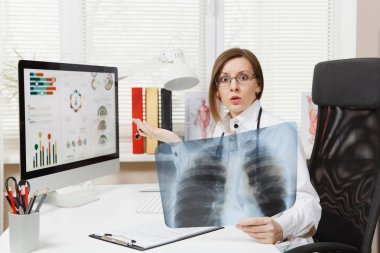 Female doctor sitting at desk, working on computer, holding X-ray of lungs, fluorography, roentgen in light office in hospital. Woman in medical gown, stethoscope in consulting room. Medicine concept.