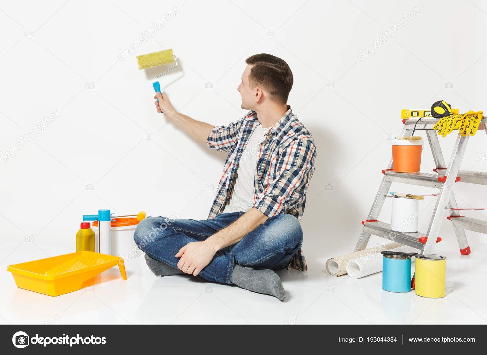 Man Sitting On Floor Using On Wall Paint Roller Instruments For