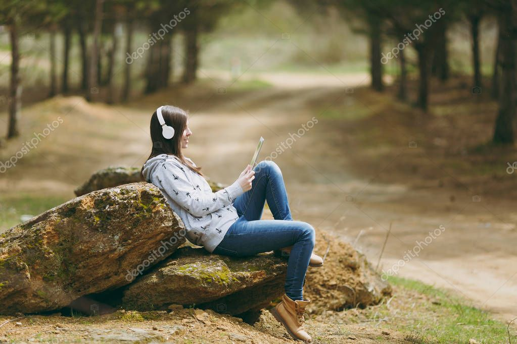 Young smiling beautiful woman in casual clothes with headphones