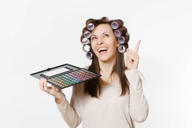 Fun young woman with curlers on hair with palette colorful eyeshadows isolated on white background. Makeup with set facial decorative cosmetics. Beauty fashion lifestyle concept. Area with copy space.