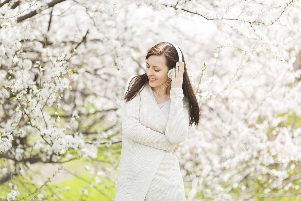 Young smiling relaxed beautiful woman in light casual clothes clinging to headphones listening music in city garden or park on blooming tree background. Spring nature, flowers. Lifestyle concept