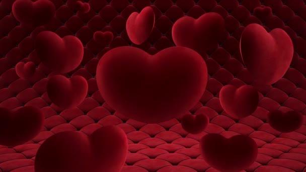 Červená sametová srdce visí ve vzduchu kolem jednoho velkého srdce. Na pozadí hladce se pohybujícího prošívaného povrchu. Video smyčka.