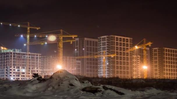 Výstavba obytných budov v večer - věžové jeřáby - čas kola