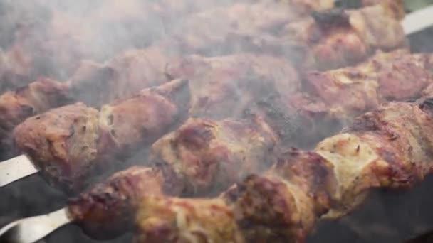 Kuchař otáčí špejlemi Shashlik na grilu ve zpomaleném filmu, zavřít.
