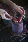 Fotografie Dort s ovocem, pokryté modrofialové glazury a čokolády s květinami, Cosmic dort, ručně dělané pečivo s ženou ruce, tmavé pozadí, Selektivní ostření