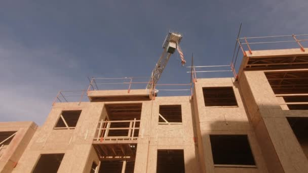 Construction site wide pan view of wood frame and crane used for hoisting materials.  4k.