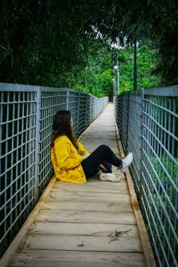 Girl sits on narrow wooden suspension bridge looking into the distance