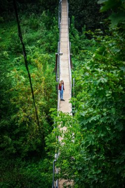 Girl walks on a wooden bridge surrounded by trees