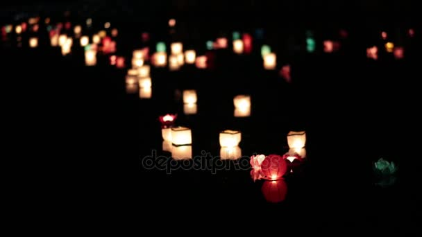 Many lanterns floating down the river at night.