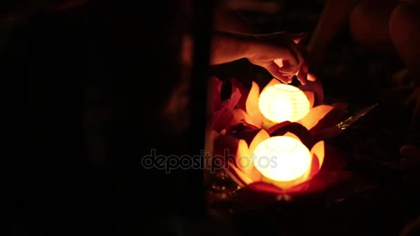 People hands and water lanterns at night. Water lanterns festival.