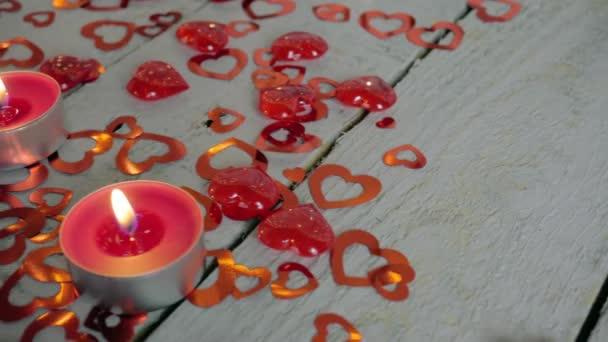 Pomalé detailní snímek osvětlené svíčkami na dřevěný stůl s červeným srdcem a okolí. Valentinky den