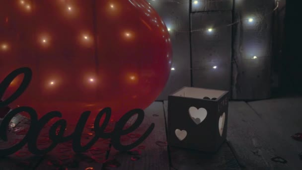 Slow close-up slide shot of Love sign with red hearts, lights and red baloon on background. Valentines day.
