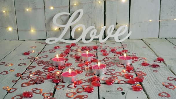 Znamení lásky s červené srdce kolem a svíčky a zapálil si. Světla na pozadí. Valentinky den