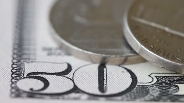 Coins on the background of a fifty dollar bill