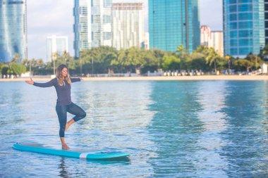 Sunrise SUP Yoga practice  in Waikiki tree pose